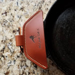 A brown leather cast iron assist handle holder on a cast iron skillet