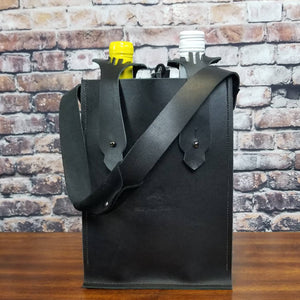 A wine bottle bag for two wine bottles in black leather with gunmetal bottle strap hardware