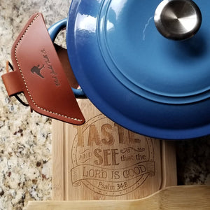 A brown leather cast iron assist handle holder on a Dutch oven