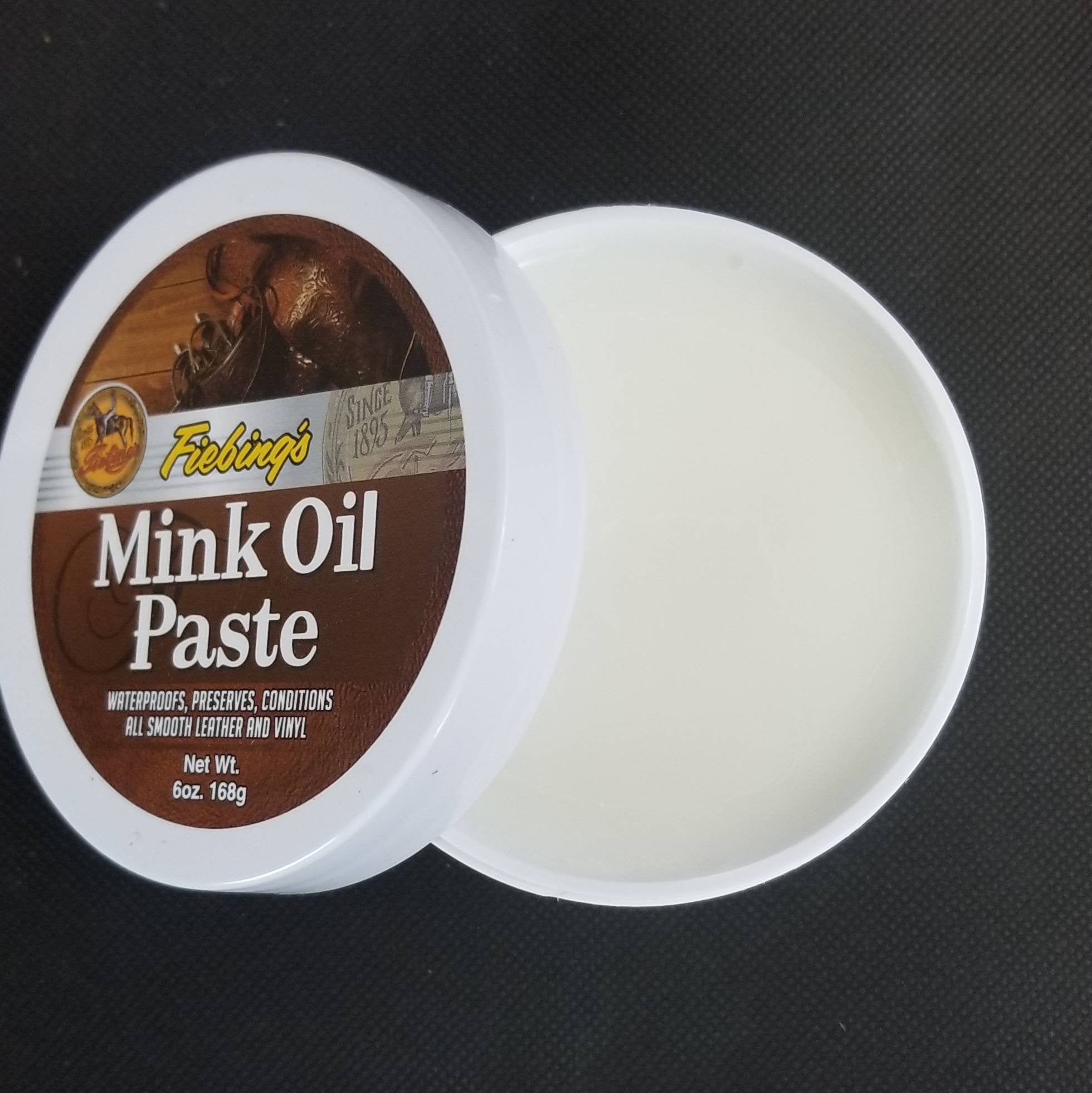 Open tub of Fiebing's mink oil paste shows white paste