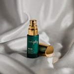 Veriphy Skincare 20/20 Eye Cream green glass bottle with gold cap floating in front of green botanical leaves