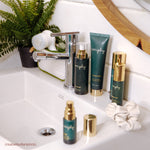 Veriphy Skincare CTRL+ALT+DEL Facial Cleanser, Power Trip Facial Serum, Self Absorbed Facial Moisturizer, 20/20 Eye Cream in green glass bottles with gold pumps standing next to bathroom sink with marble tile surround