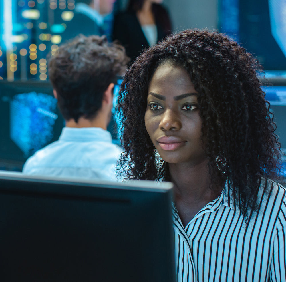 Black woman in business attire sitting in office looking at computer monitor