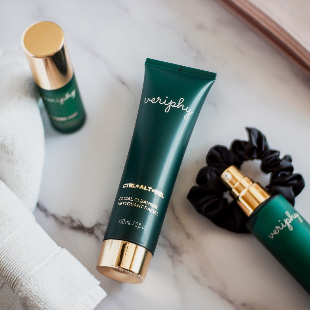 Veriphy Skincare CTRL+ALT+DEL Facial Cleanser in green recyclable squeeze tube with gold cap laying down on marble surround