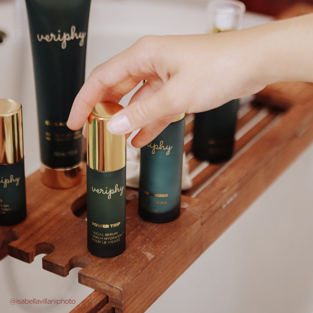 Veriphy Skincare Self Absorbed Facial Moisturizer, Power Trip Facial Serum, 20/20 Eye Cream in green glass bottles with gold caps laying on pink surface next to dark red lipstick in black and gold tube and teal and cork Pixie Mood bag