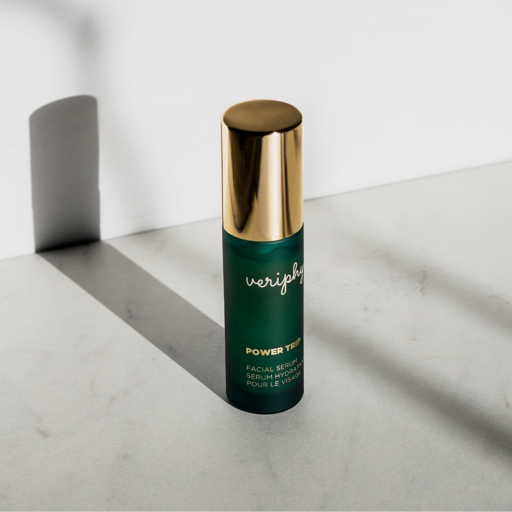 Hand holding Veriphy Skincare Power Trip Facial Serum in green glass bottle with gold cap in front of white shelf with Self Absorbed Facial Moisturizer and 20/20 Eye Cream