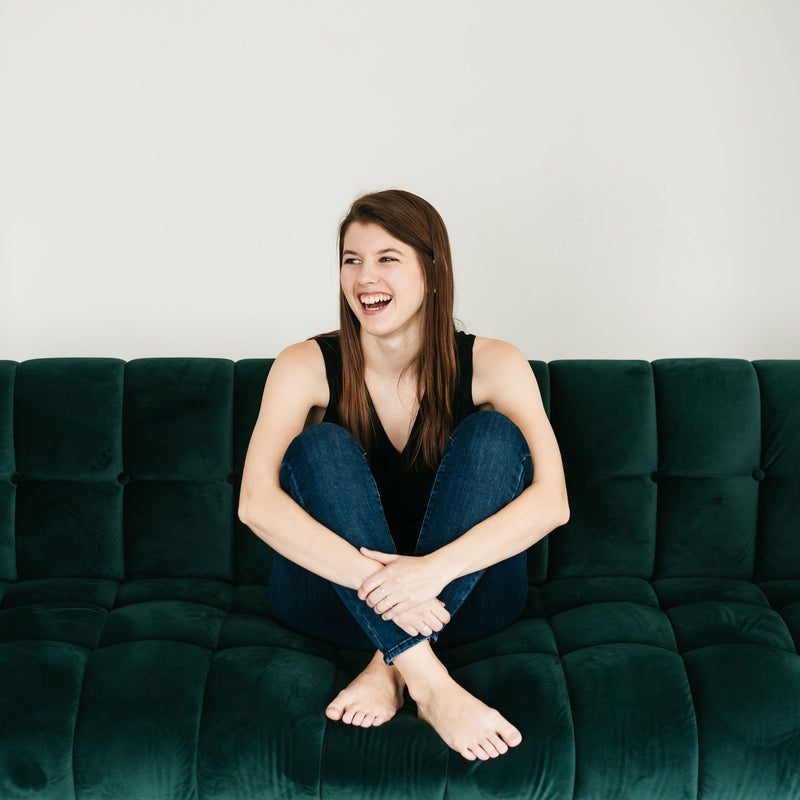 Woman smiling sitting on dark green couch with legs crossed