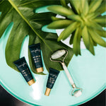 Veriphy Skincare Self Absorbed Facial Moisturizer, Power Trip Facial Serum, and 20/20 Eye Cream deluxe travel sizes in green tubes with gold caps laying next to jade roller and plants