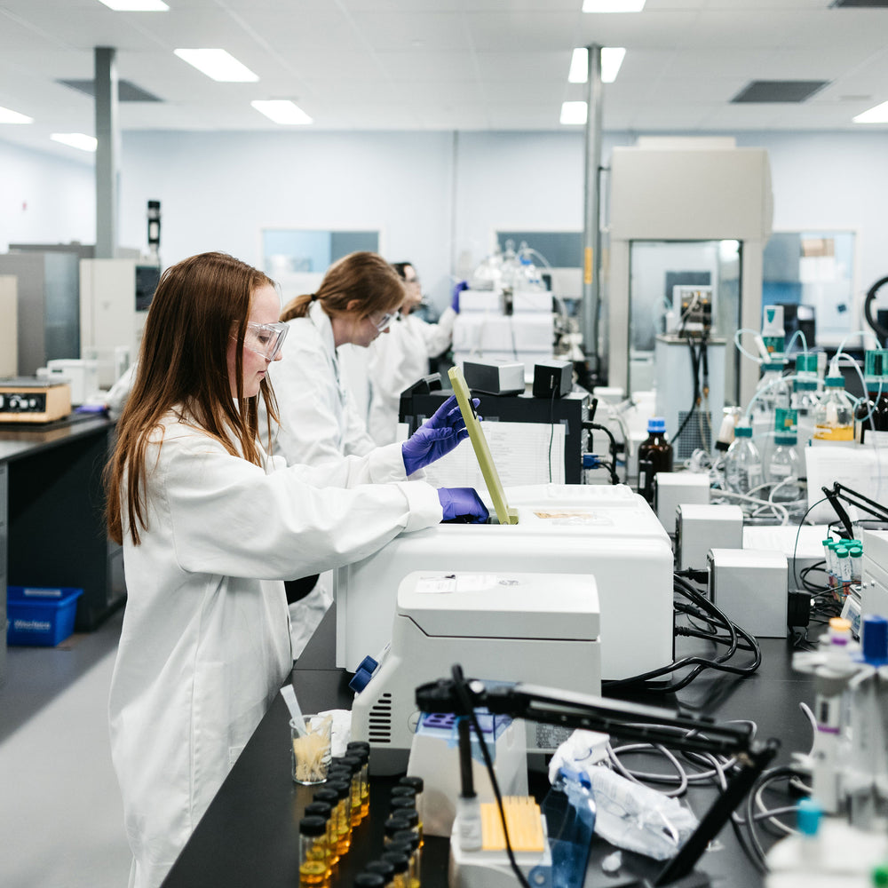 Three women in lab coats and goggles working on instrumentation in a laboratory