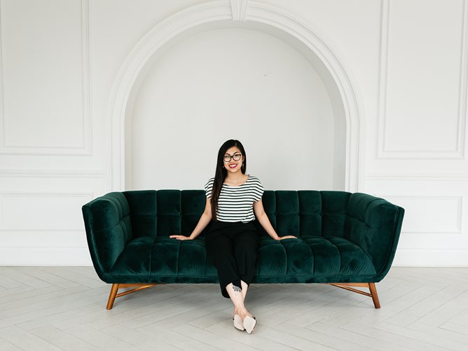 Woman, Christina Pham, sitting and smiling on a dark green couch