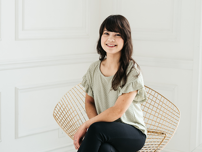 Woman, Emily Moore, in a light green shirt sitting on gold chair