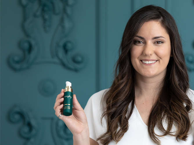 Woman, Tanya Kizovski, holding Veriphy Skincare Power Trip against dark teal background