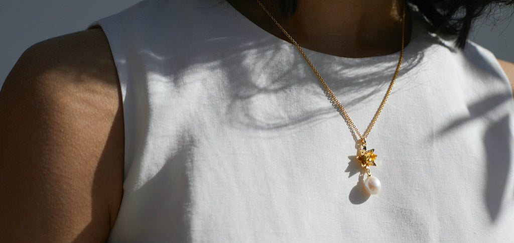 Woman wearing Bloom Lotus Pearl Pendant by Brave Edith in Gold