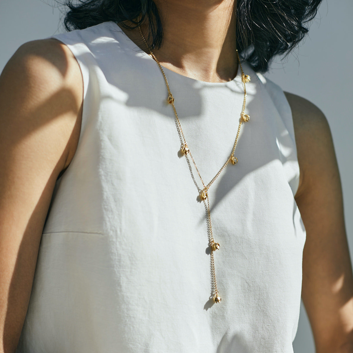 Woman wearing gold Lotus bud necklace by Brave Edith from Bloom collection