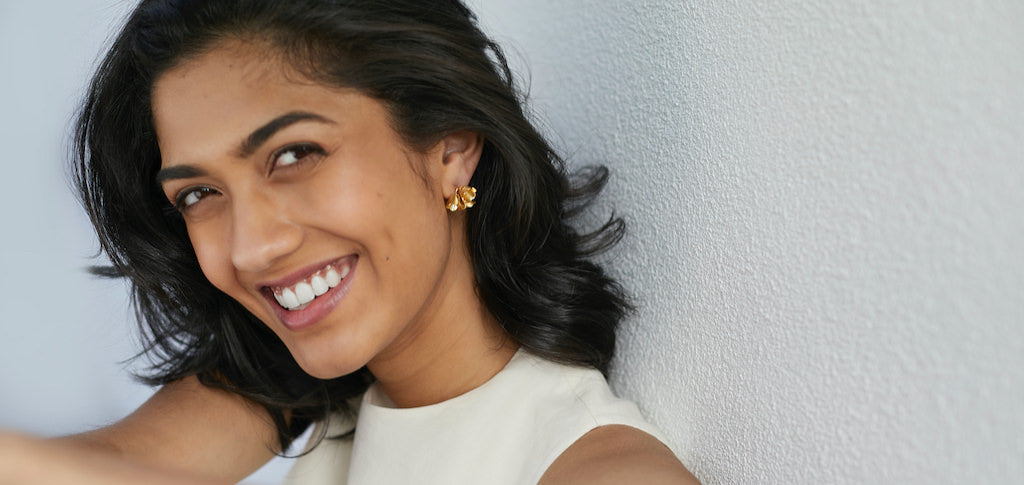 Smiling wearing gold padauk cluster studs from Brave Edith