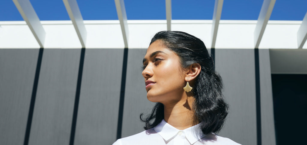 Woman wearing Gold Plume Hook Earring with sky in background