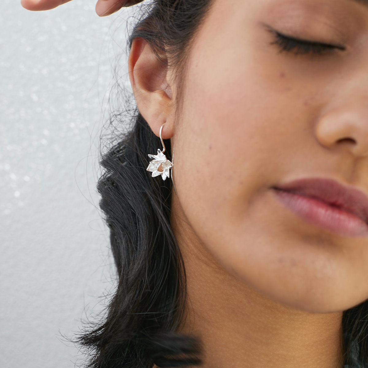 Woman wearing Brave Edith silver lotus hook earrings from bloom collection