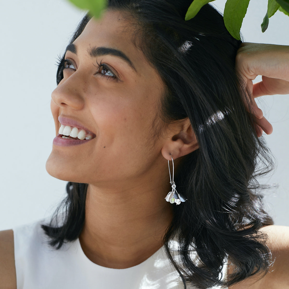 Smiling woman wearing silver Padauk hook earrings by Brave Edith