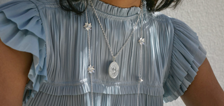Woman with blue top wearing Brave Edith silver necklaces