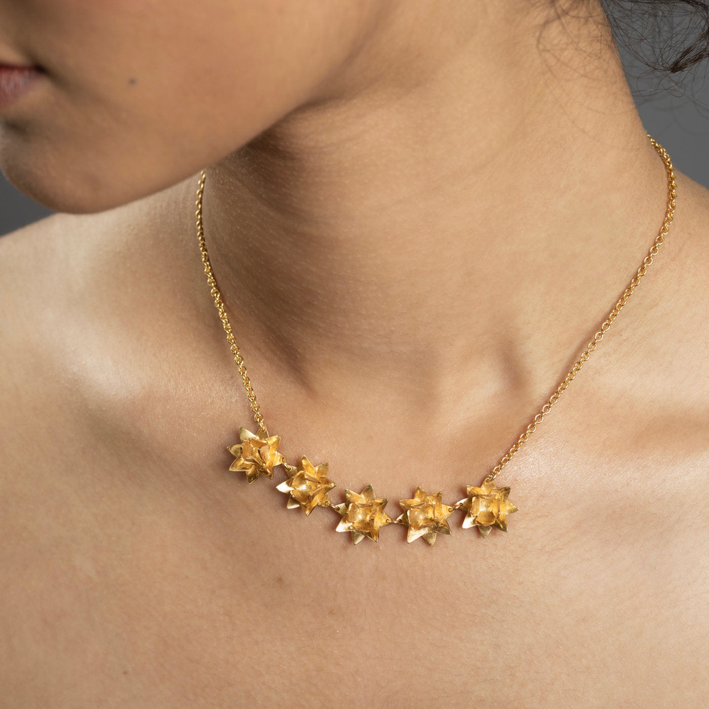 Close up gold five lotus flowers on necklace