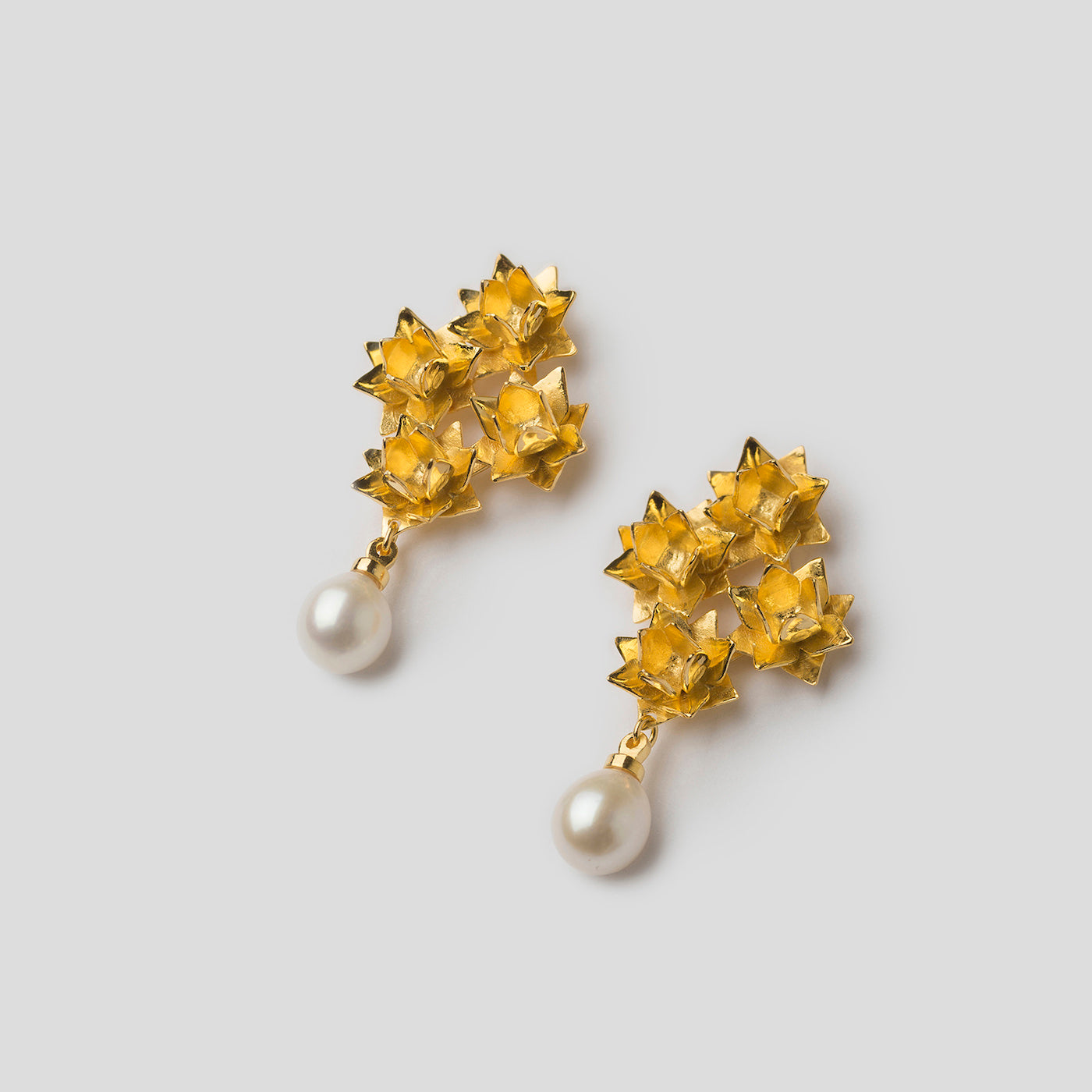 Gold four lotus pearl earrings on angle on white background