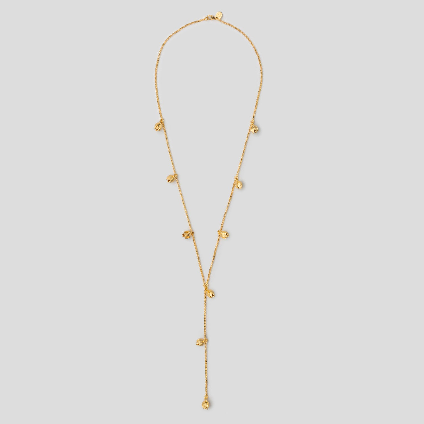 Gold lotus bud lariat necklace on white background