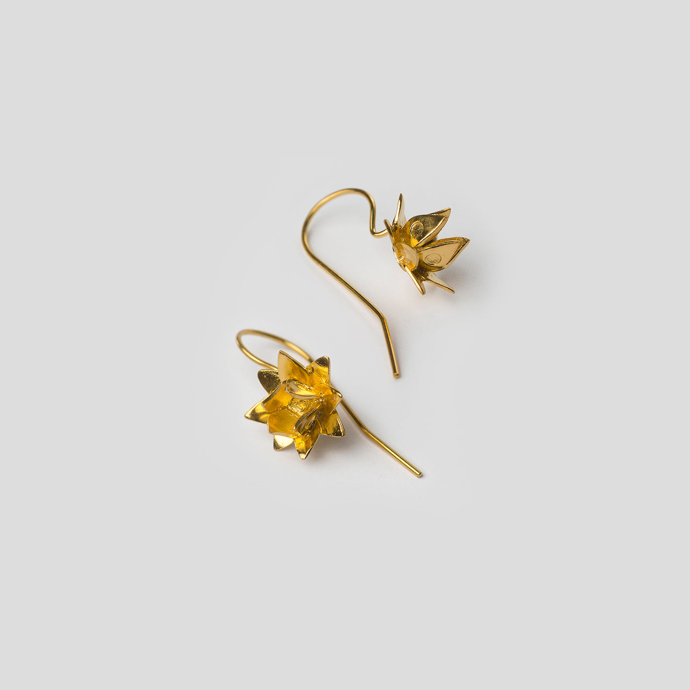 gold lotus hook earrings on white background