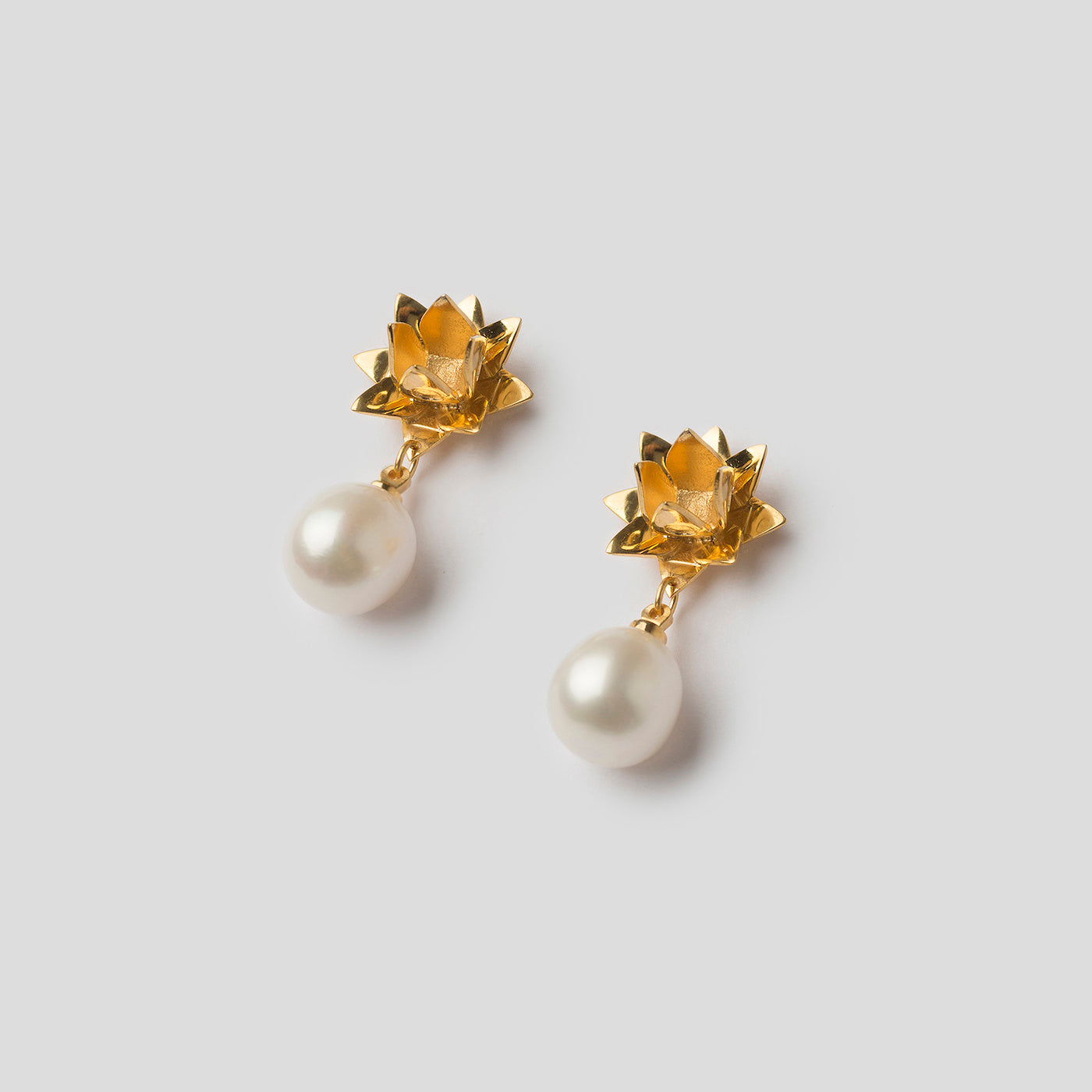 Front of gold lotus pearl earrings on angle on white background