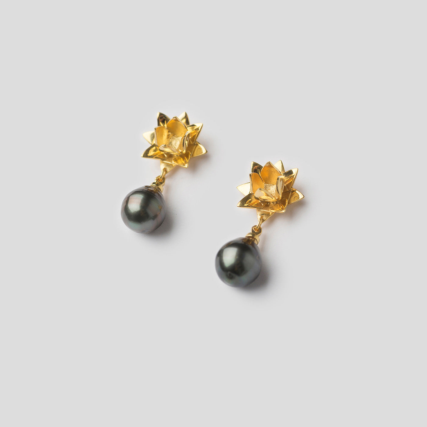 gold lotus earrings with Tahitian pearl on white background