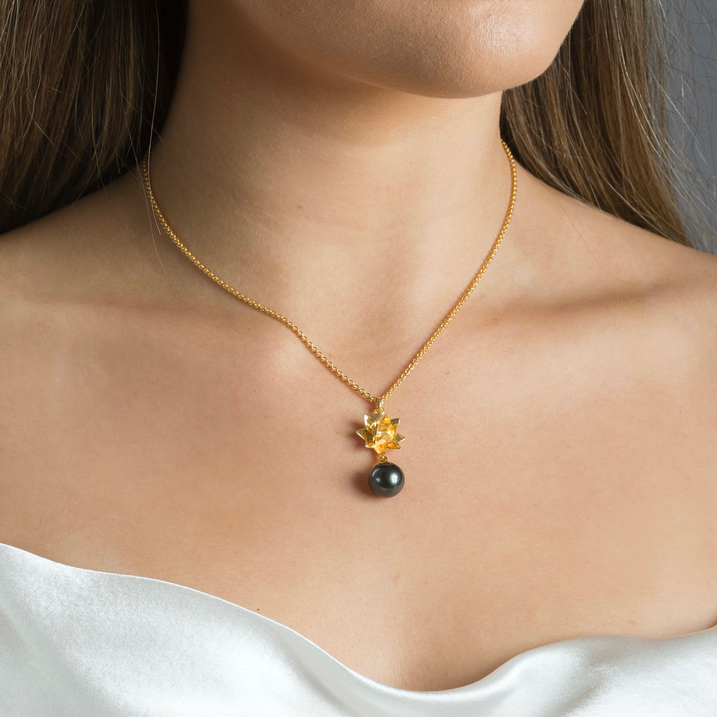 close up of gold lotus necklace with Tahitian pearl on white background