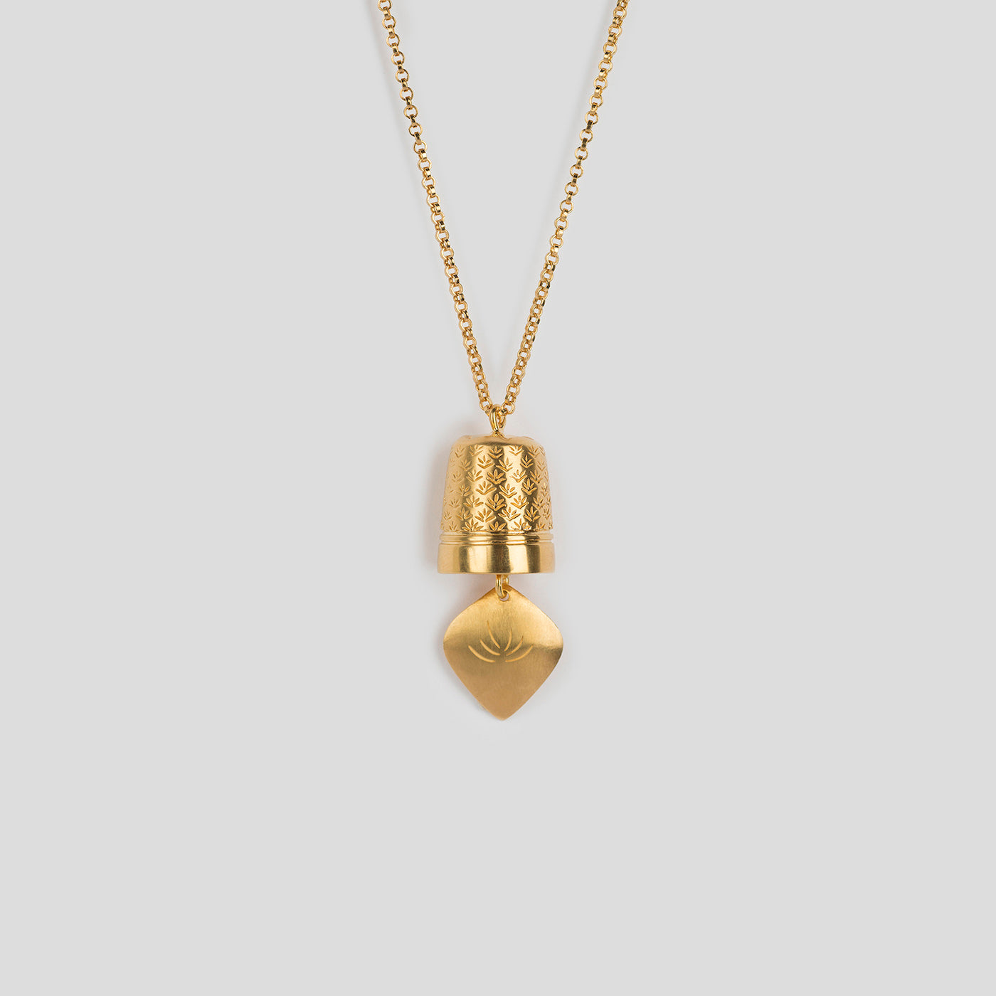 close up of gold precious bell pendant on white background