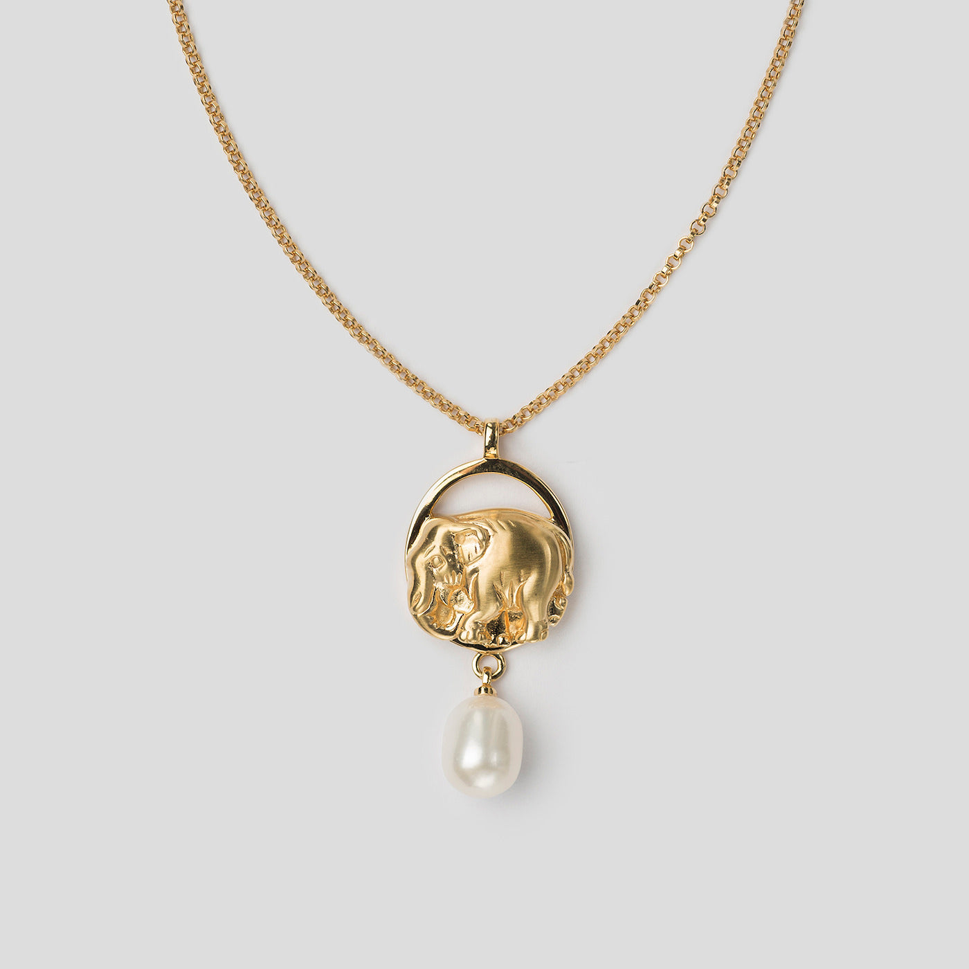 close up of gold precious elephant pendant on white background