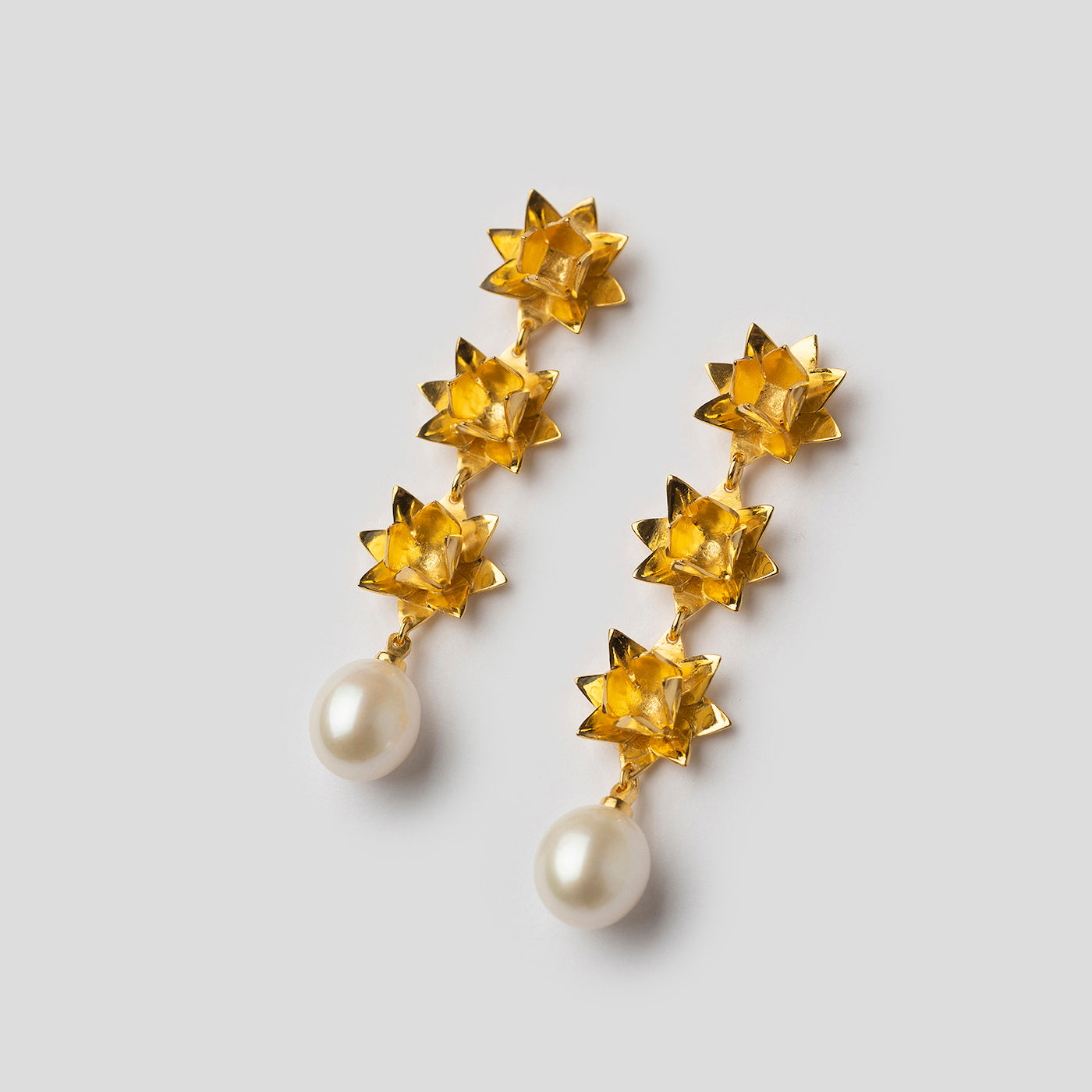 gold triple lotus earrings with pearls on angle on white background