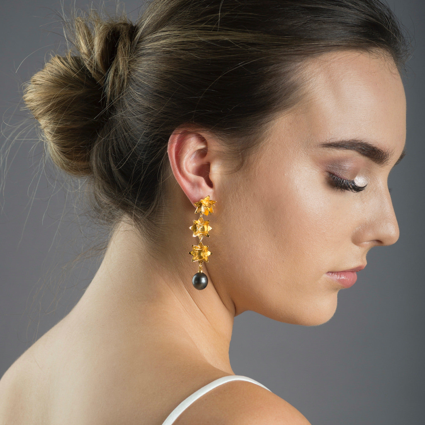 Gold triple lotus earrings with tahitian pearls on angle