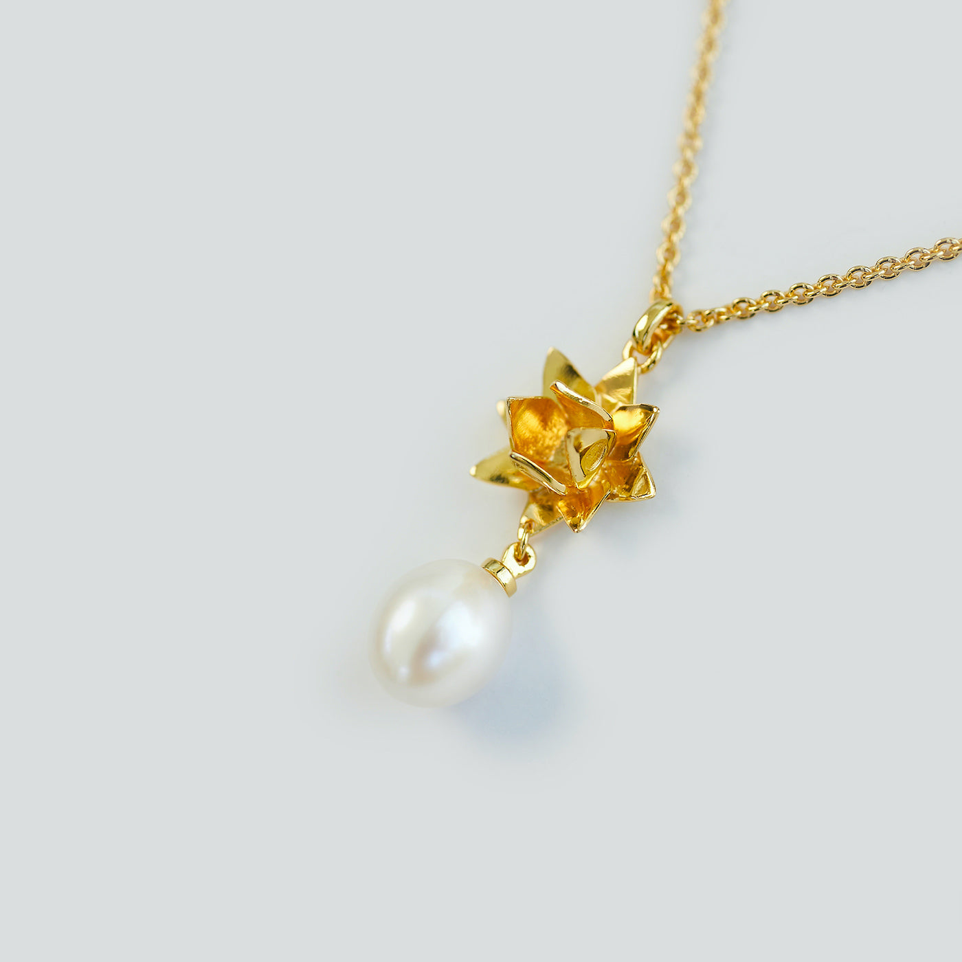 Close up of 18K gold vermeil lotus Pearl pendant by Brave Edith on white background