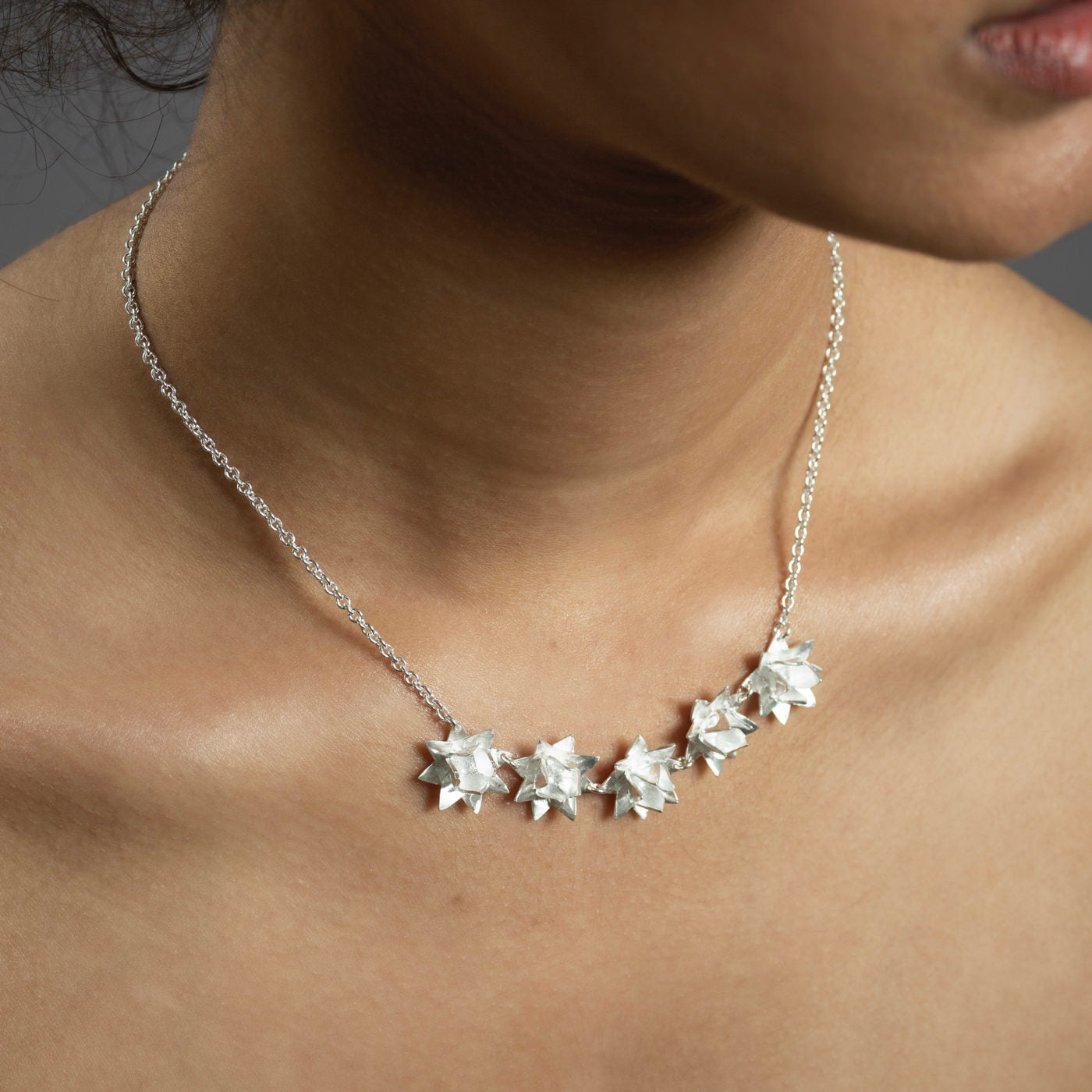 close up of five silver lotus flowers on necklace