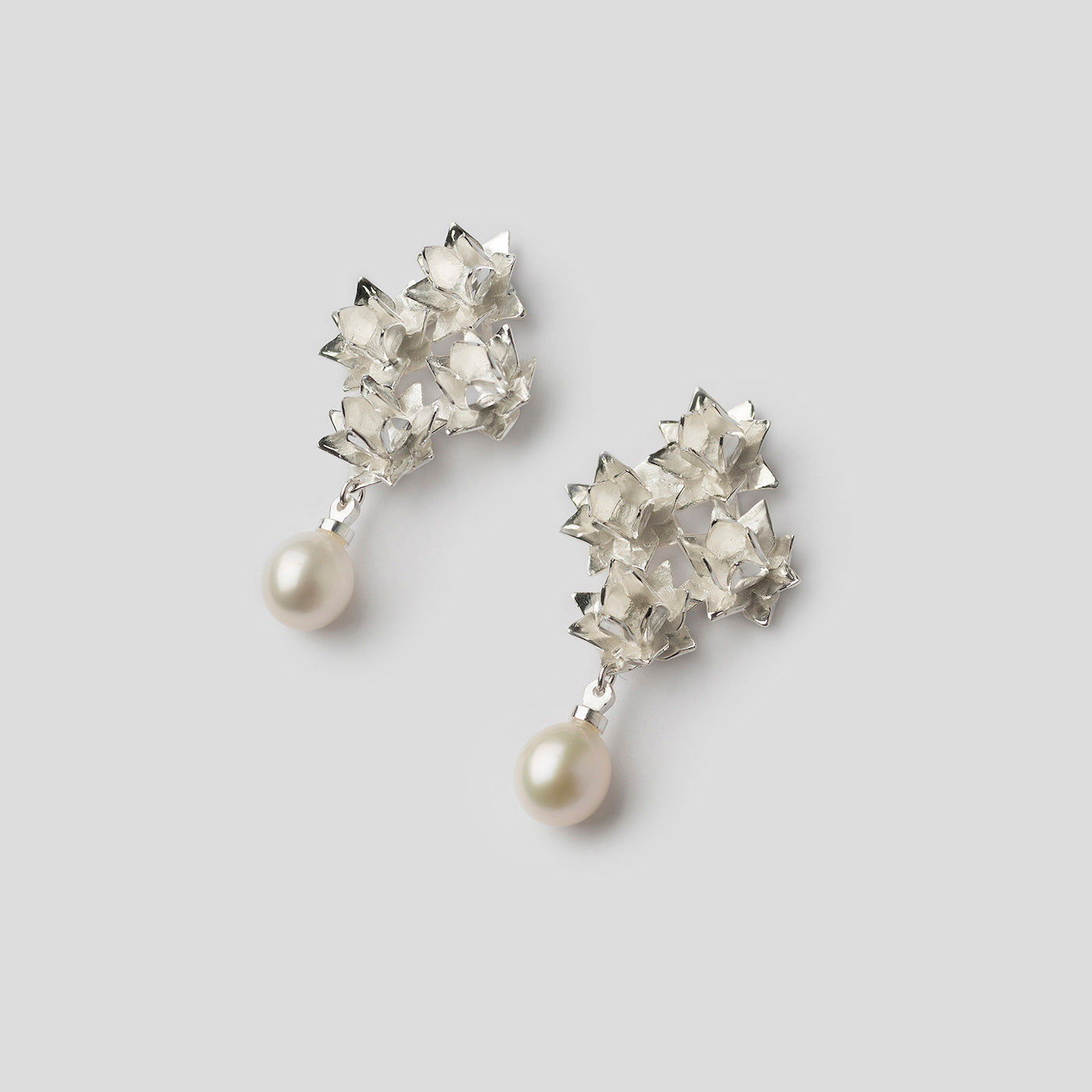 silver four lotus pearl earrings on angle on white background