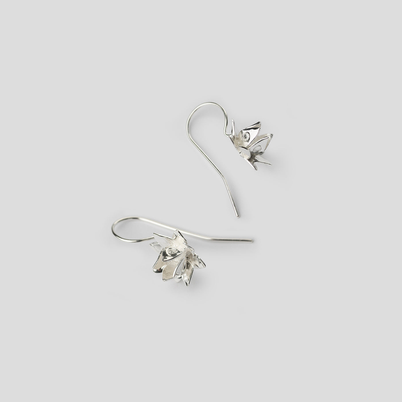 silver lotus hook earrings on white background