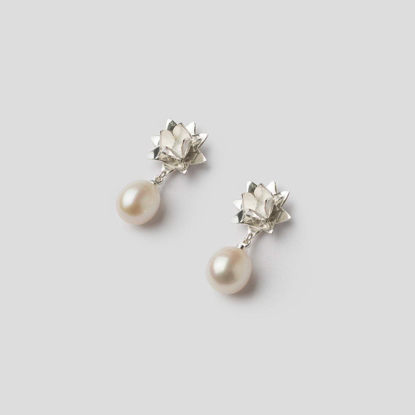 silver lotus pearl earrings on angle on white background