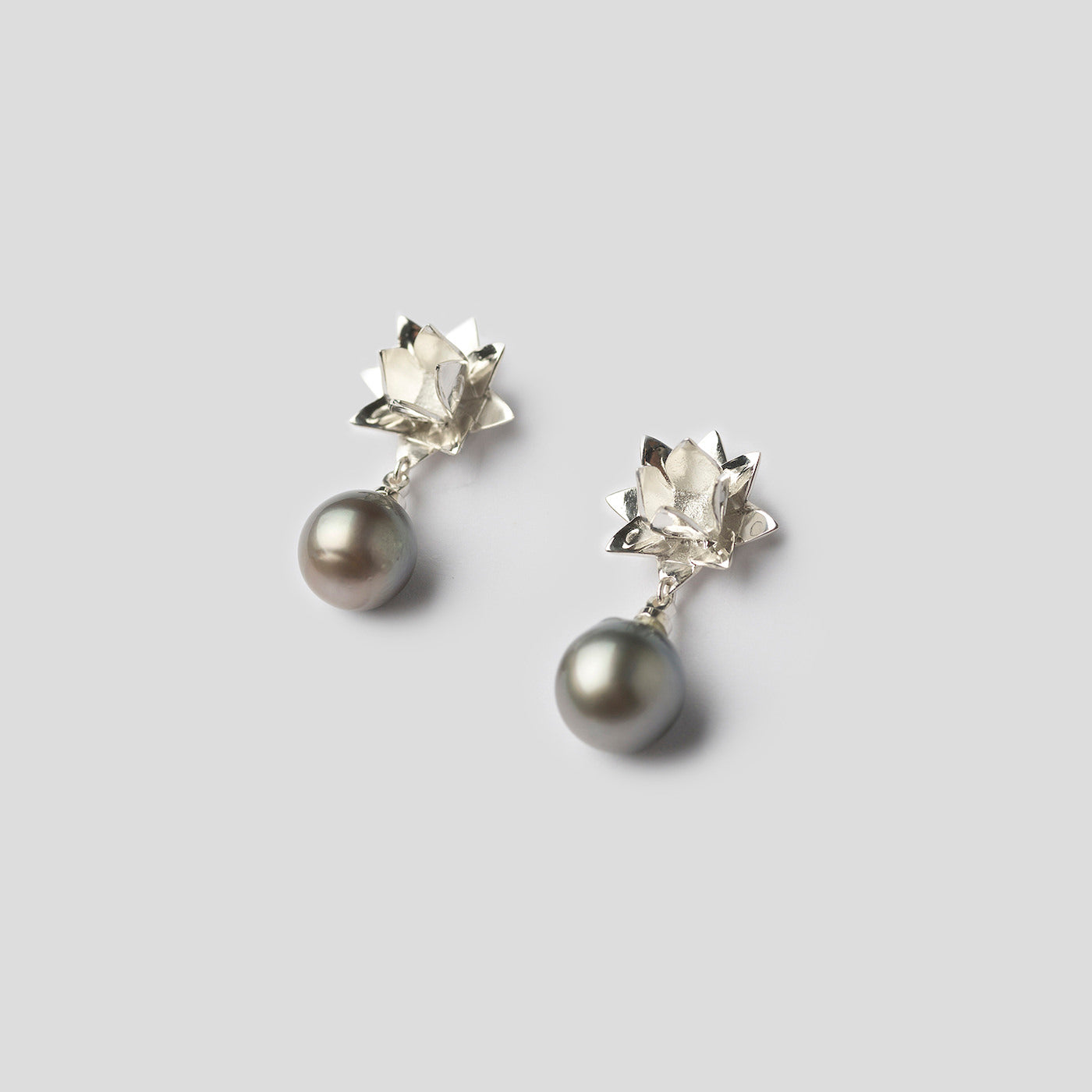 silver lotus earrings with Tahitian pearl on white background