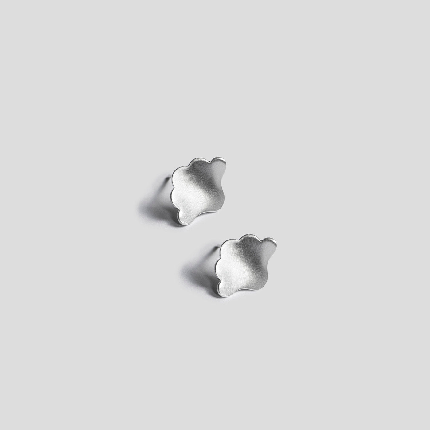 silver plume earrings on white background