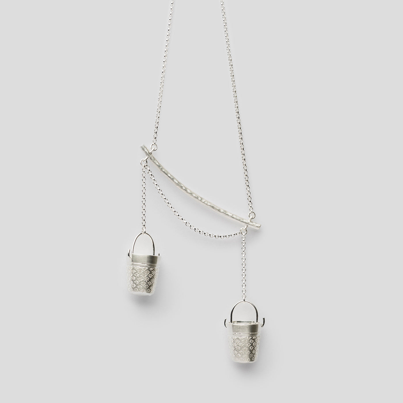 close up of silver precious buckets pendant on white background