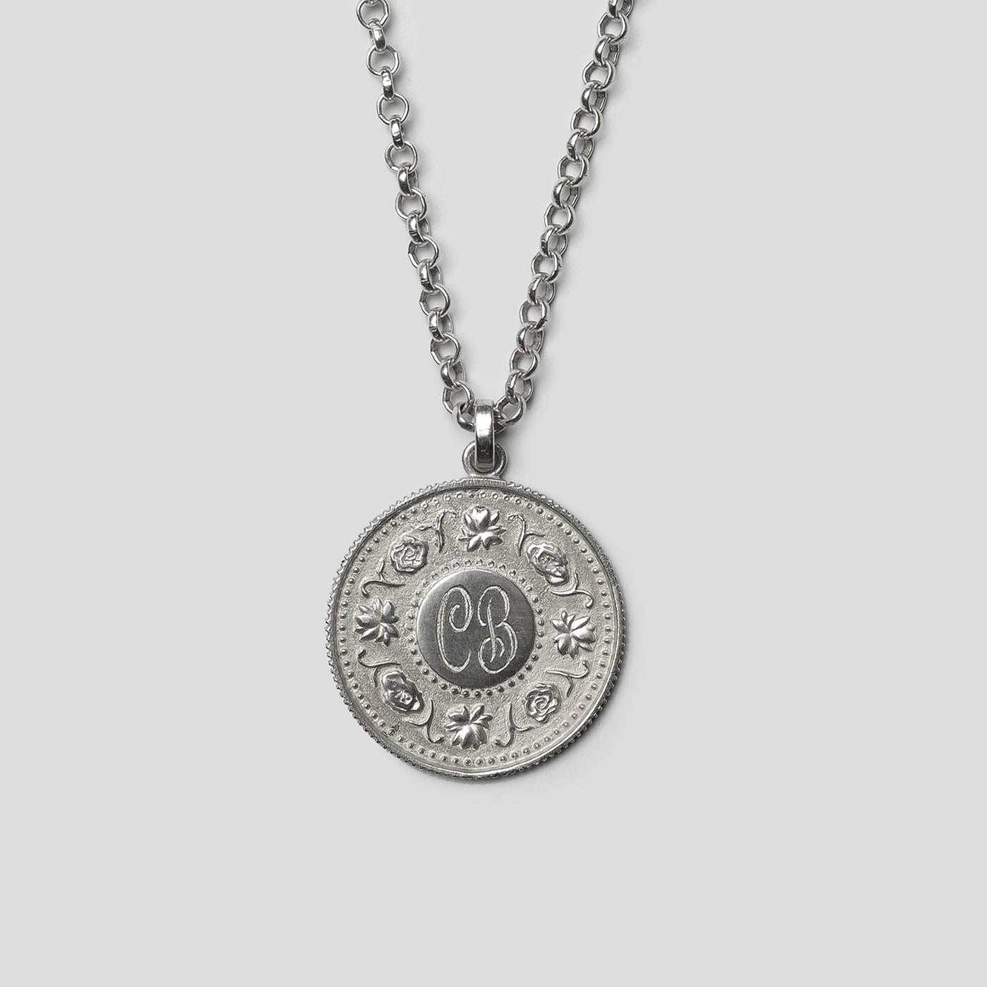 front of Silver precious coin necklace on white background
