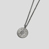 Silver precious coin necklace on angle on white background
