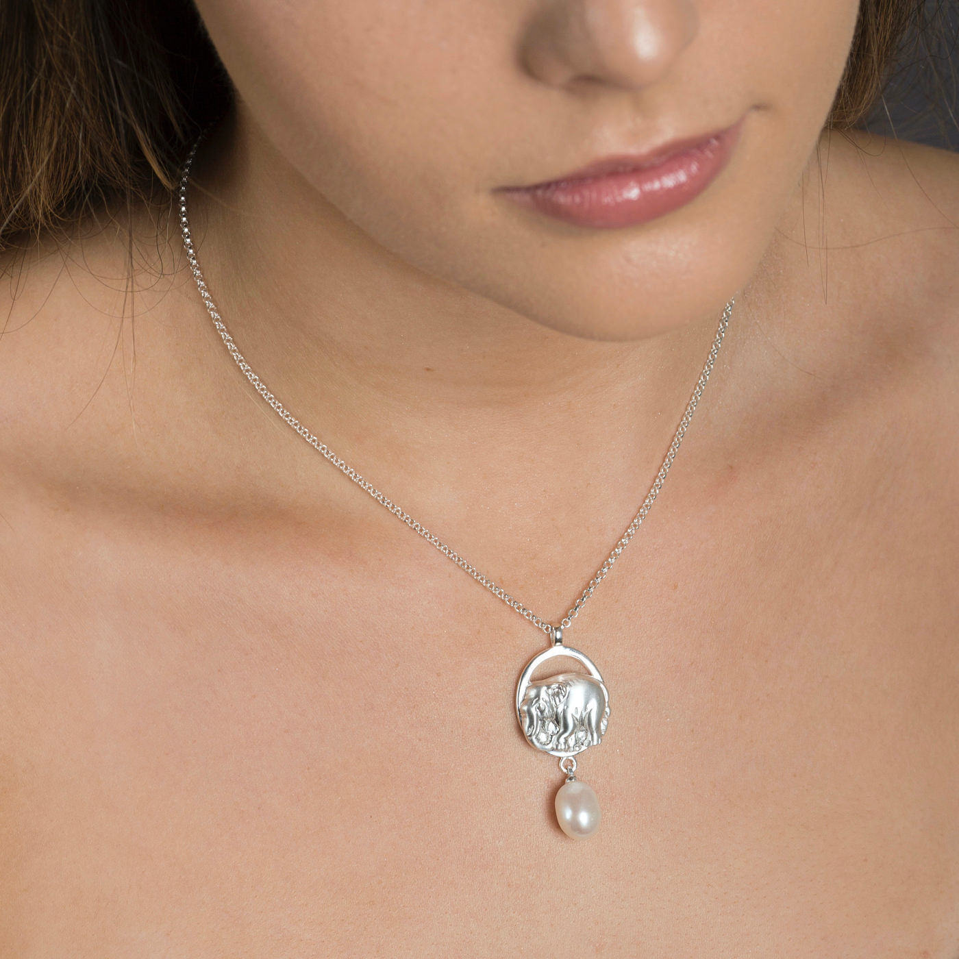 close up of silver precious elephant pendant on white background