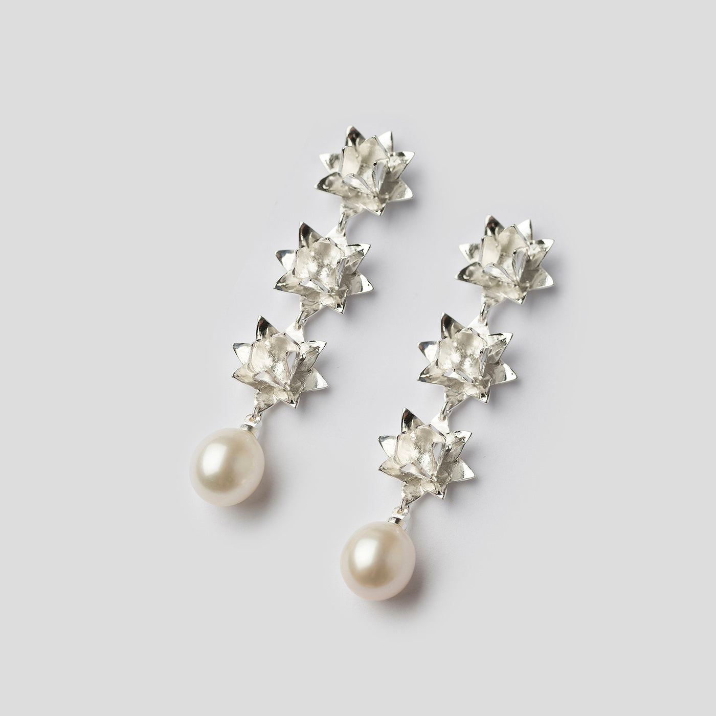 silver triple lotus pearl earrings on angle on white background