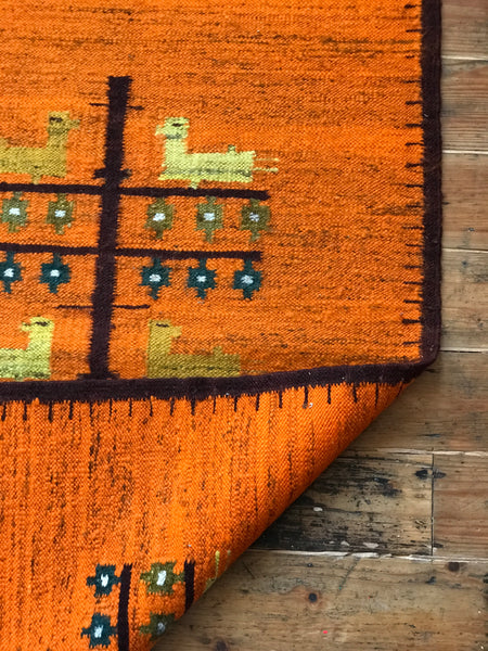 Orange wool rug with white fringe