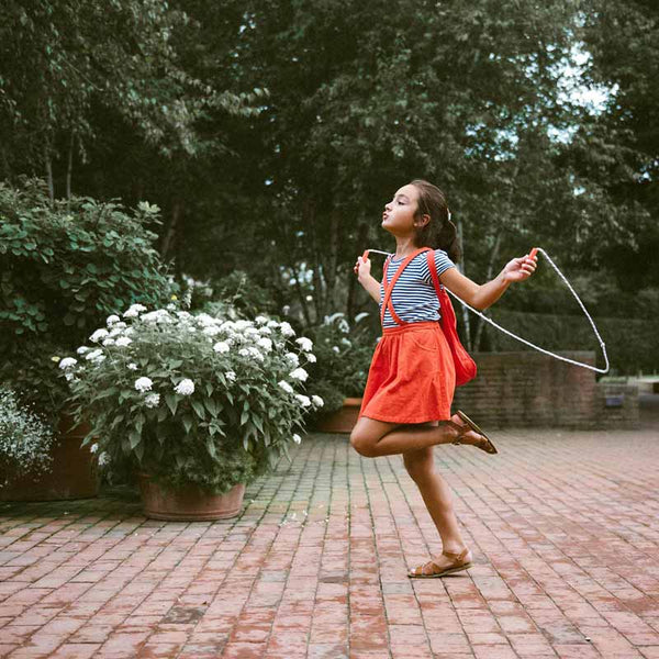 Notabag mini 2 in one tote and backpack in red shown as backpack on a young girl skipping