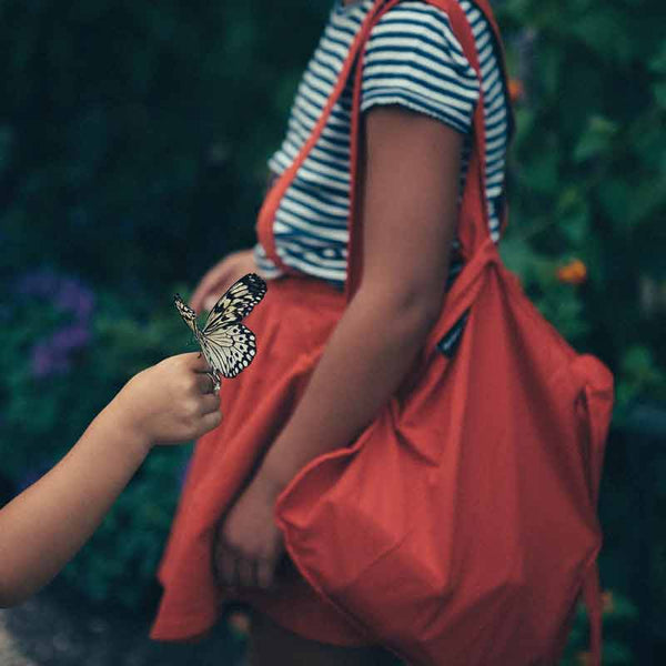Notabag mini 2 in one tote and backpack in red shown on a young girl