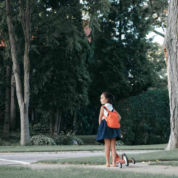 Notabag mini 2 in one tote and backpack in red shown as backpack on a young boy